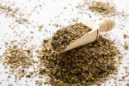 condiment: healthy dried oregano condiment on white table with scoop
