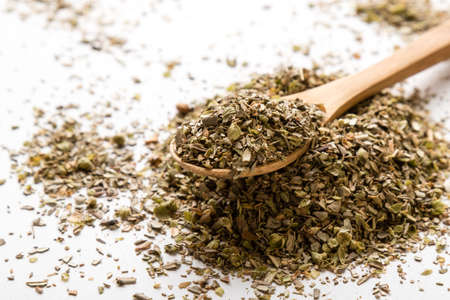 condiment: healthy dried oregano condiment on white table with spoon