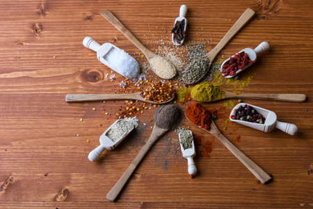 diferent: assortment of diferent color spices on wooden table Stock Photo