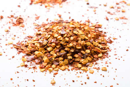 crushed red peppers: crushed dried chili flakes on white table