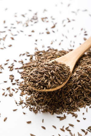 caraway: aromatic natural caraway seeds on white table with spoon