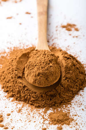 brown cinnamon condiment powder on white table with spoon