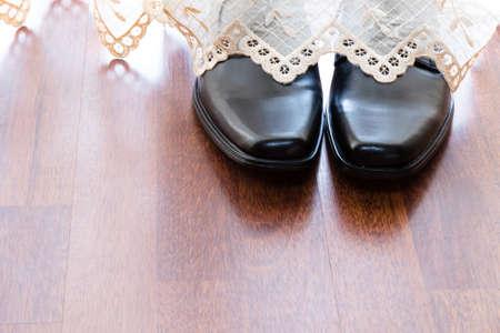 shiny black: mans black leather shiny shoes behind curtain Stock Photo