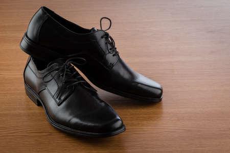 mans: mans black leather shoes on wooden floor