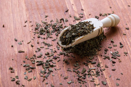 condiment: healthy dried oregano condiment on wooden table with scoop