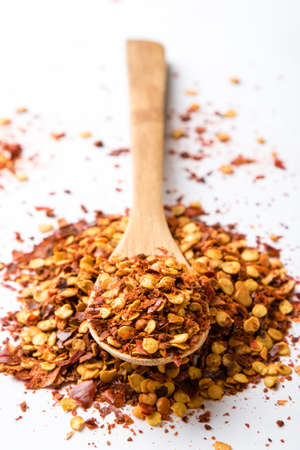 crushed red peppers: crushed dried chili flakes on white table with spoon