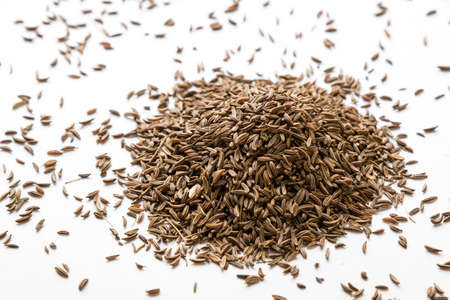 caraway: aromatic natural caraway seeds on white table