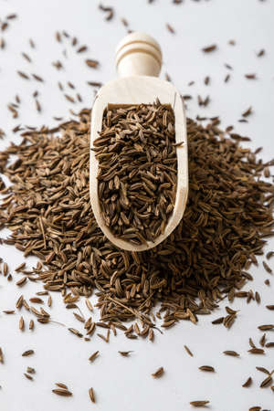 caraway: aromatic natural caraway seeds on white table with scoop Stock Photo