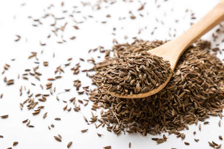 aromatic: aromatic natural caraway seeds on white table with spoon