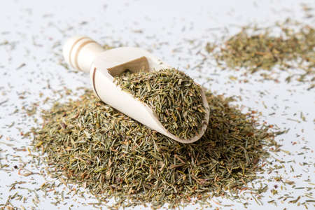 aromatic: natural dried aromatic thyme on white table with scoop