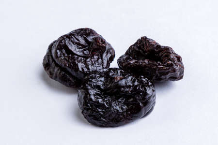 prunes: organic sweet dark prunes on white table Stock Photo