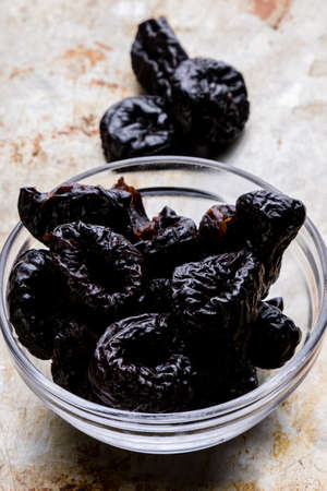 prunes: organic sweet dark prunes on steel plate Stock Photo