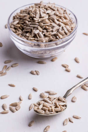 hulled: hulled sunflower seeds in a glass bowl and on spoon