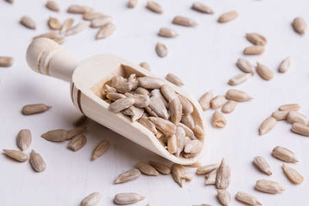hulled: hulled sunflower seeds on wooden scoop on white table