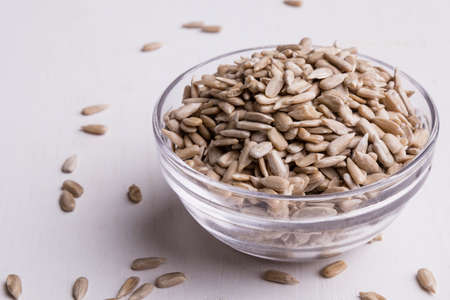 hulled: hulled sunflower seeds in a glass bowl on white table