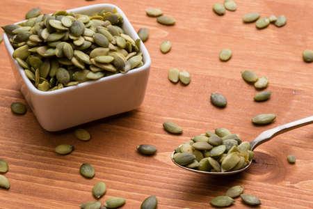 Semillas de calabaza verdes saludables en la mesa de madera con cuchara y tazón de fuente blanco