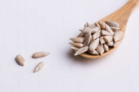 hulled: hulled sunflower seeds on wooden spoon on white table
