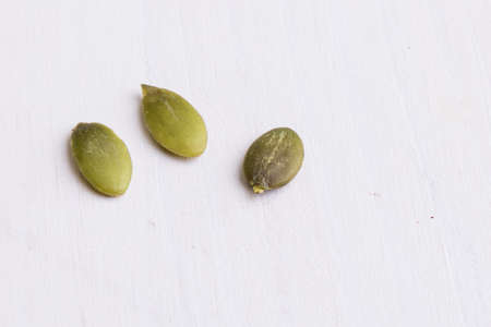 tabel: green healthy pumpkin seeds on white table