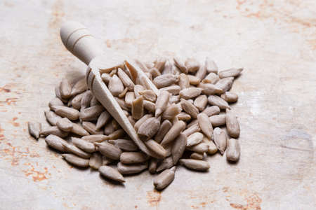 hulled: hulled sunflower seeds on steel plate and wooden scooop Stock Photo