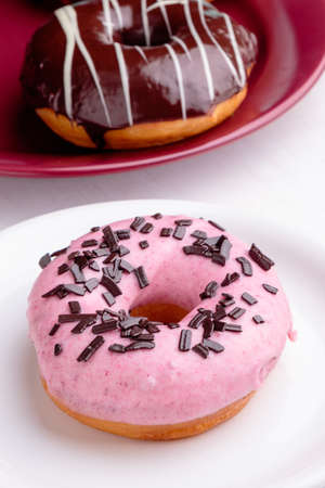 frosting': donut with pink frosting on white plate