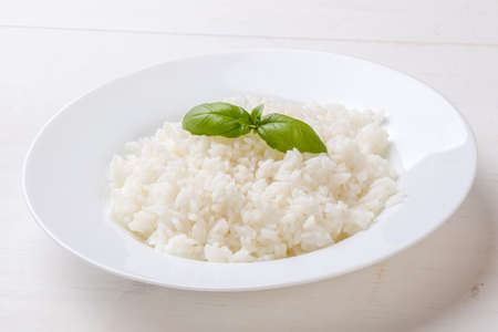 cooked rice with basil on white plate
