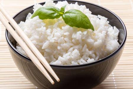 riz cuit petit morceau de basilic dans un bol noir