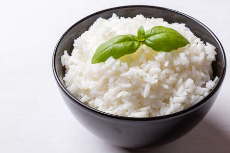 cooked rice whit basil in black bowl Stockfoto