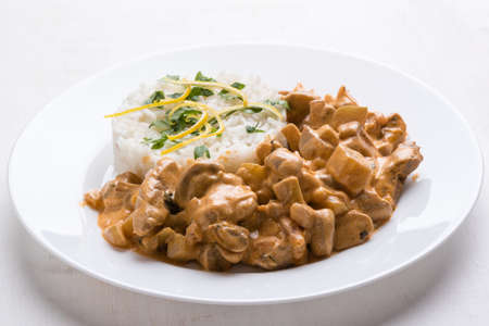 beef stroganoff with rice on white plate