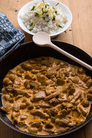 beef stroganoff in big pan with rice in a bowl