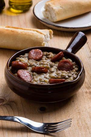 green lentil: green lentil stew with sausage in brown bowl