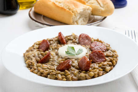 green lentil: green lentil stew with sausage in white plate Stock Photo