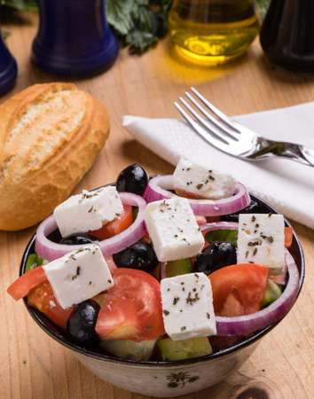 fresh healthy greek salad in bowl on wooden table