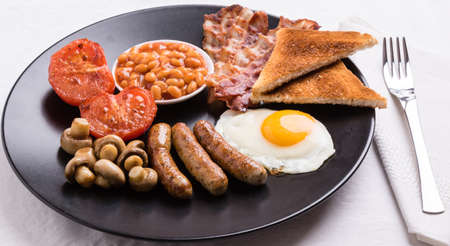 full english breakfast with bacon, sausage, eggs, beans, mushrooms on black plate