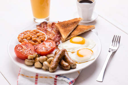 tabel: full english breakfast with bacon, sausage, eggs, beans, mushrooms, on white tabel Stock Photo
