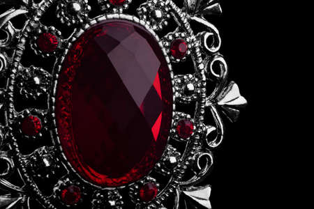 macro image of pendant with red gemstone on black background