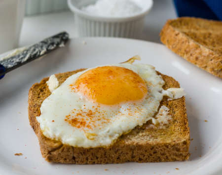 toast with egg sunny side up breakfast on white plate