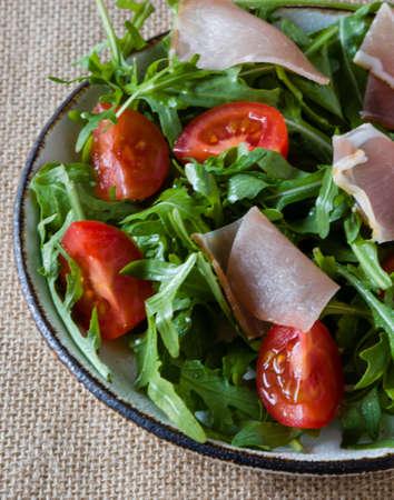 fresh healthy ruccola salad with tomato and ham Stock Photo