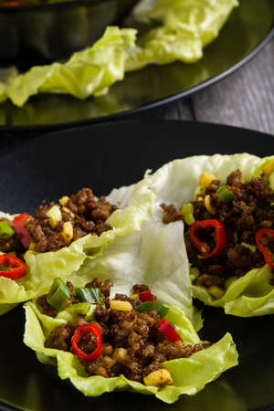 korean salad: chilli beef lettuce wraps on black plate Stock Photo