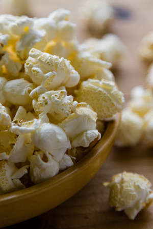 fresh salted popcorn in bowl on wooden table