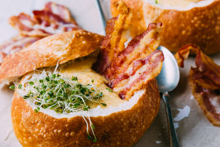 cream soup in bread bowl with bacon and broccoli sprouts Stock Photo