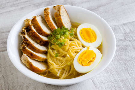 japanese ramen soup with chicken and boiled egg in white bowl