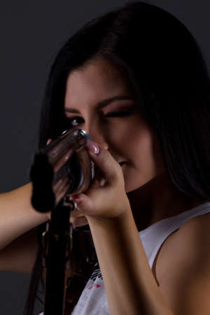 beautiful young woman portrait with shotgun in studio