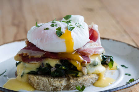 benedict: rustic tasty eggs benedict on plate on wooden table Stock Photo