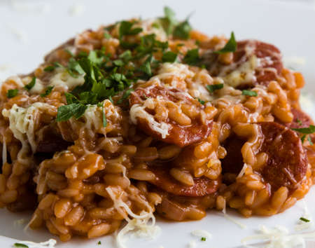 Chorizo risotto with tomato and red wine on white plate Stock Photo