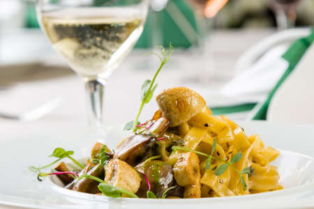 gourmet tagliatelle pasta with mushrooms in white palte