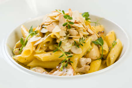 gourmet penne with gorgonzola and mushrooms in white plate