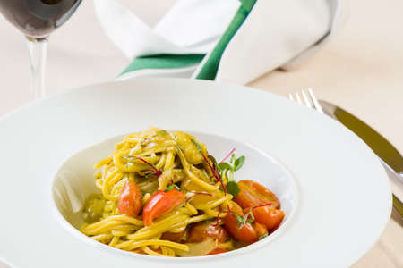 gourmet spaghetti with cherry tomatoes in white plate