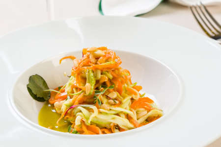 spaghetti from carrots and zucchini with pesto in white plate
