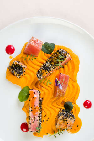 gourmet red tuna with carrot purée in white plate