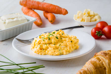 fresh scrambled eggs on white plate on breakfast table